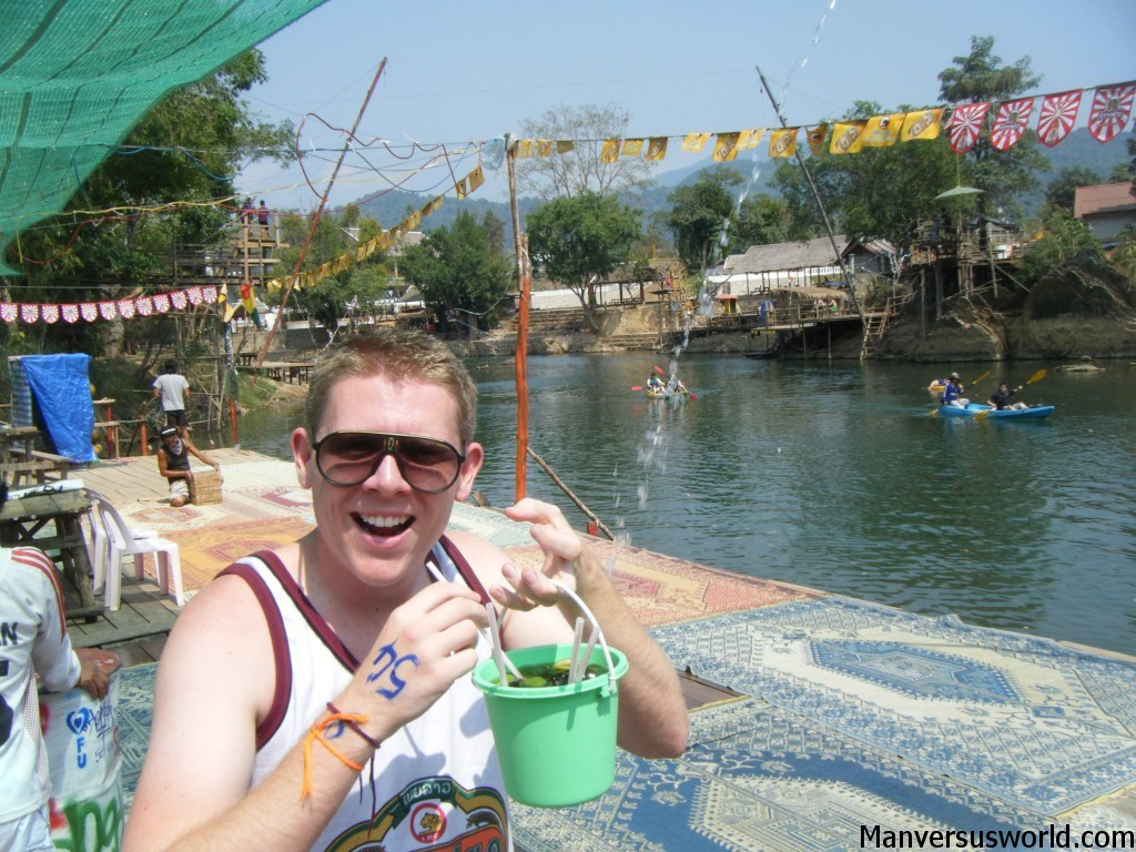 I drink from a bucket in Vang Vieng, Laos