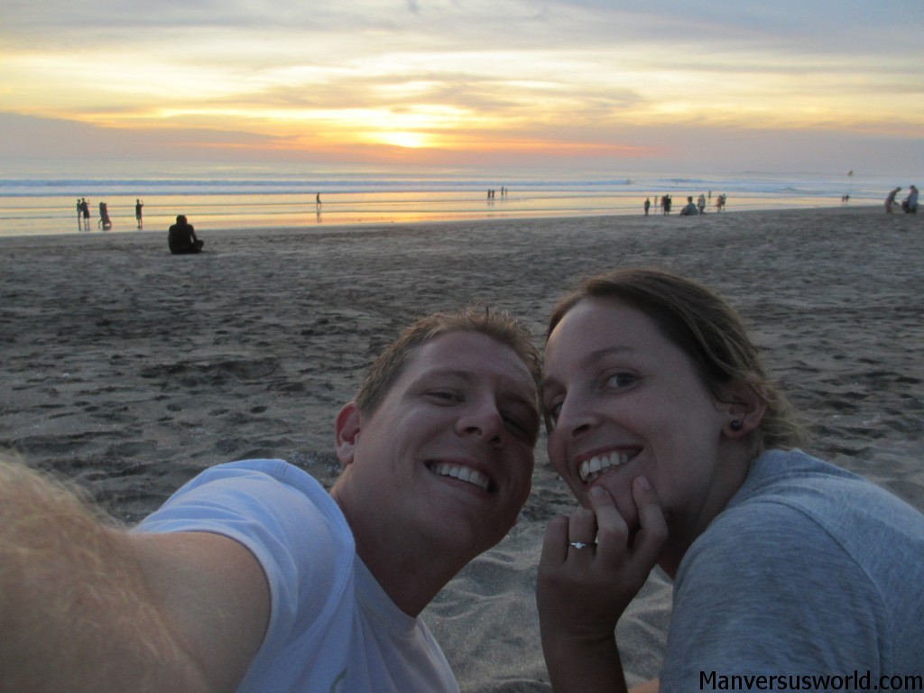 Happy couple of travelers on Kuta Beach, Bali