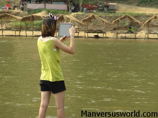 A woman uses an iPad to take a photo while travelling in Asia